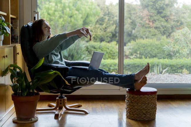 Metà donna adulta allungamento della mano mentre seduto sulla sedia a casa — Foto stock
