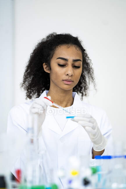 Young female researcher pouring liquid with pipette in laboratory — Stock Photo