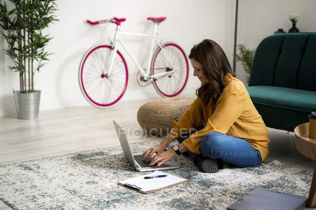 Посмішка жінки з поперечними ногами сидячи на підлозі, використовуючи ноутбук у вітальні. — стокове фото