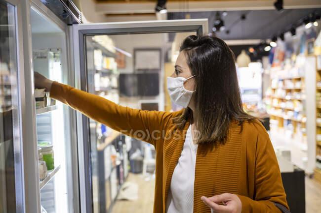 Молода жінка шукає їжу в холодильнику. — стокове фото