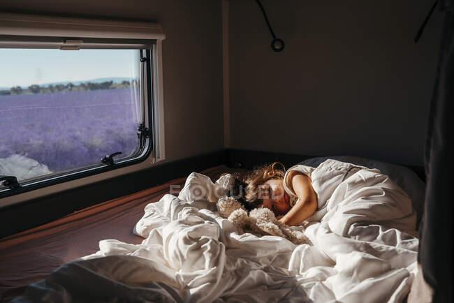 Dolce bambina che dorme in camper con giocattolo di coniglio ripieno — Foto stock