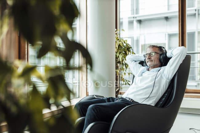 Homem de negócios relaxado com as mãos atrás da cabeça ouvindo música através de fones de ouvido enquanto sentado na cadeira de massagem no corredor do escritório — Fotografia de Stock