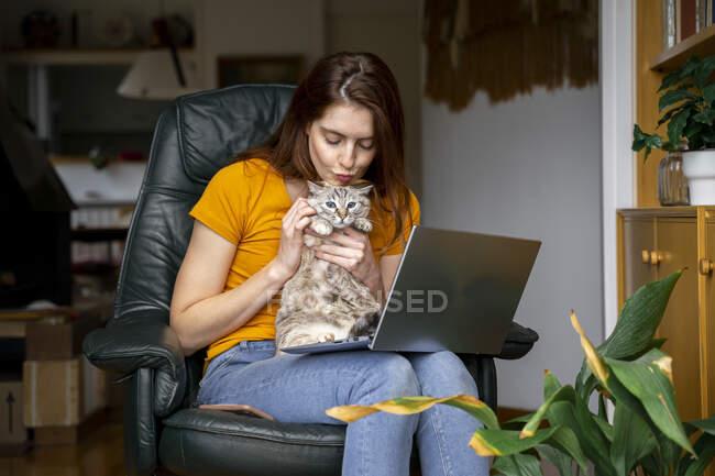 Молода жінка обіймає кота, сидячи на стільці з ноутбуком вдома. — стокове фото
