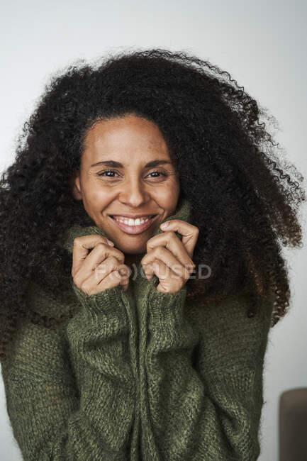 Цікава жінка в светрі на сірому тлі — стокове фото