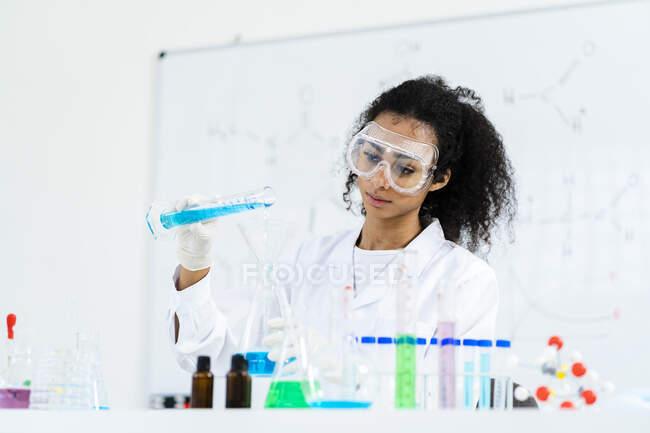 Молодая женщина-исследователь наливает жидкость во фляжку во время работы в лаборатории — стоковое фото