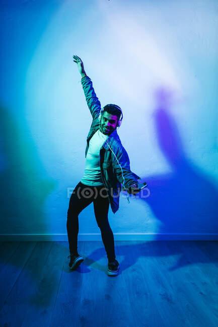 Hombre con auriculares sosteniendo el teléfono móvil mientras baila por fondo de color - foto de stock