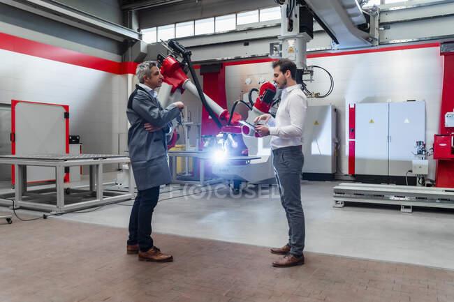 Engenheiros do sexo masculino discutindo enquanto a robótica solda na fábrica — Fotografia de Stock