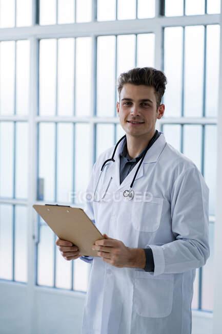 Médico varón sujetando portapapeles en el hospital - foto de stock