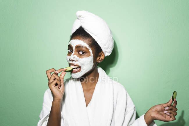Mulher com máscara facial comendo pepino de pé contra fundo verde — Fotografia de Stock
