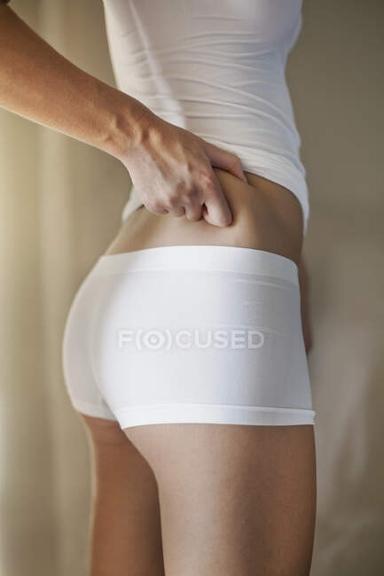 Woman hand pinching waist skin at home — Stock Photo