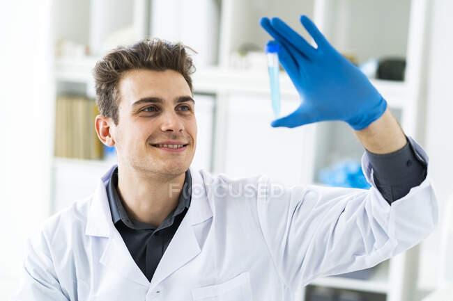 Cientista masculino sorridente examinando líquido no tubo de ensaio — Fotografia de Stock