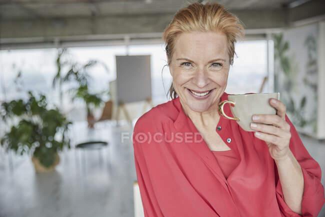 Hermosa mujer madura con taza de café en casa - foto de stock
