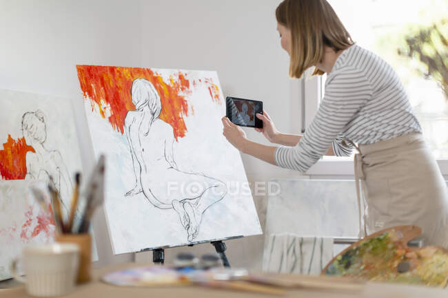 Artista feminina tirando fotos de pintura em estúdio em casa — Fotografia de Stock