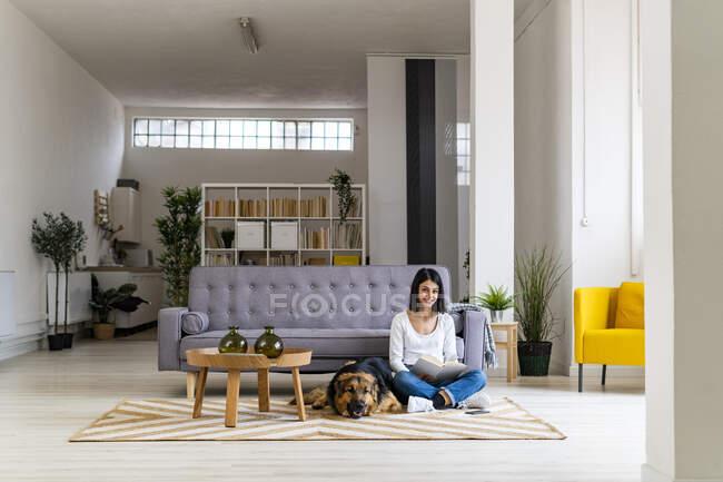 Посмішна жінка, яка читає книжку, сидячи з домашнім собакою на килимі у вітальні. — стокове фото