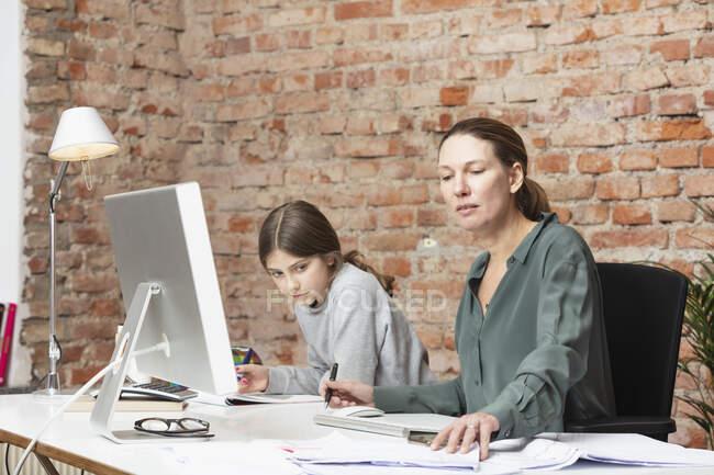 Berufstätige Frau arbeitet für Tochter, die am Schreibtisch studiert — Stockfoto