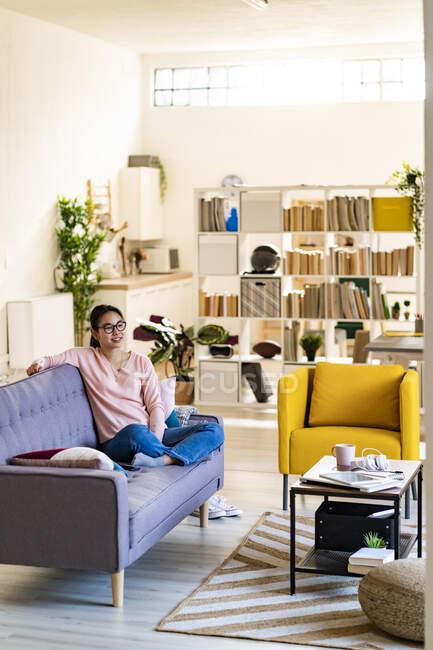 Задумчивая молодая женщина сидит скрестив ноги на диване дома — стоковое фото