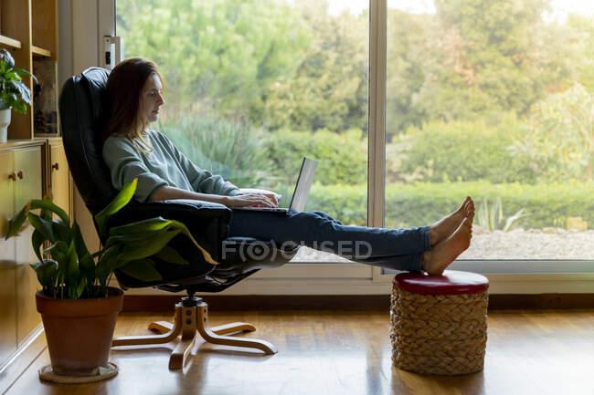 Серед дорослої жінки, яка працює на ноутбуці, сидячи вдома на стільці. — стокове фото