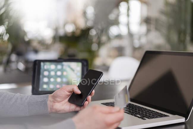 Mãos de empresário masculino on-line pagando através de cartão de crédito no telefone inteligente no escritório — Fotografia de Stock