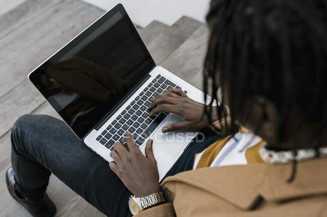 Hombre africano sentado en las escaleras usando el ordenador portátil - foto de stock