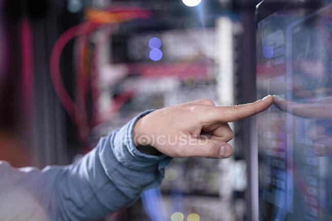 Experiencia en TI masculina tocando la pantalla del ordenador en sala de servidores - foto de stock