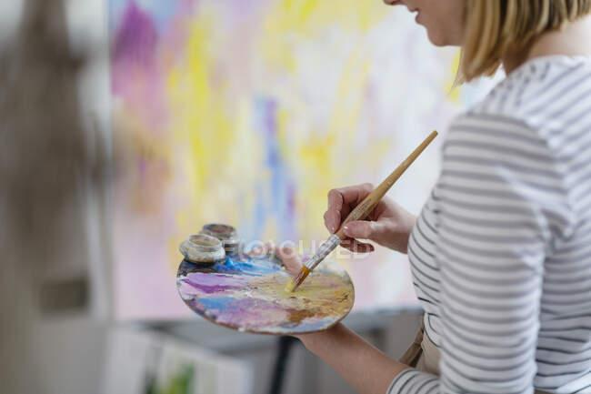Artista feminina misturando cores na paleta enquanto pinta tela abstrata no estúdio em casa — Fotografia de Stock