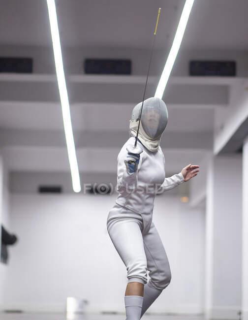 Женщина в костюме фехтовальщика сидит в спортзале — стоковое фото