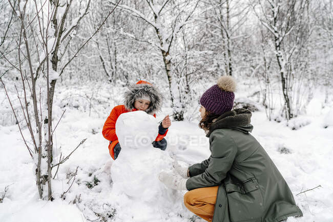 Girl with teenage sister making snowman in forest — Stock Photo