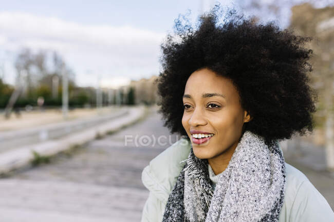 Happy young woman looking away while standing outdoors — Stock Photo