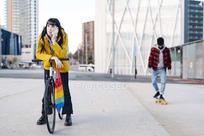Mujer hablando en el teléfono móvil mientras está de pie con su amigo skateboarding en segundo plano al aire libre - foto de stock
