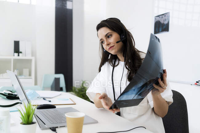 Female doctor showing x-ray image while consulting online through laptop at clinic — Stock Photo