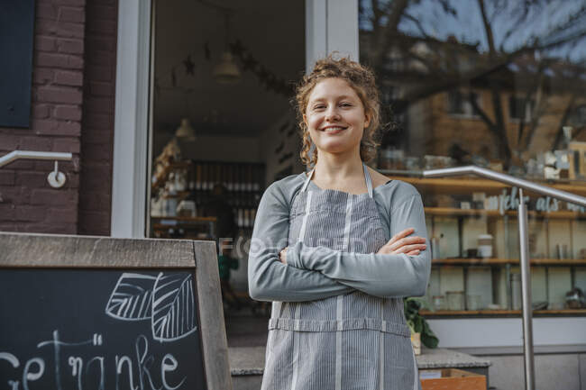 Smiling female clerk with arms crossed standing against organic store — Stock Photo