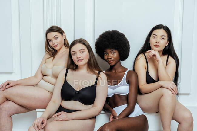 Hermoso grupo multiétnico de modelos de moda en lencería contra pared blanca - foto de stock