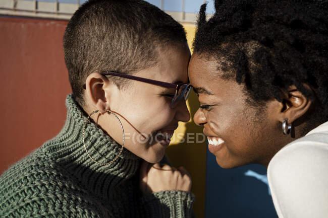 Amigos sonrientes sentados cara a cara con los ojos cerrados contra la pared - foto de stock