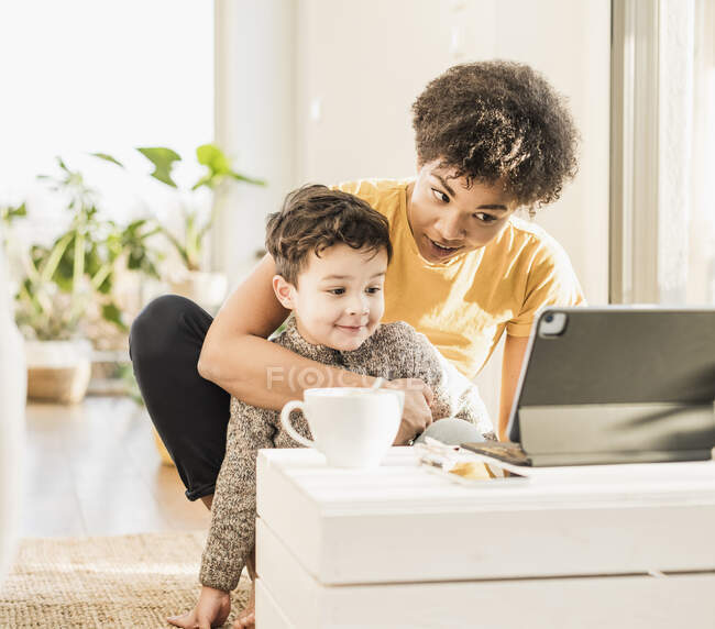 Young woman and boy using digital tablet while studying online sitting at home — Stock Photo