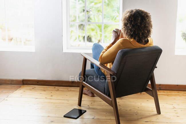 Жінка п'є чай, сидячи вдома у кріслі. — стокове фото