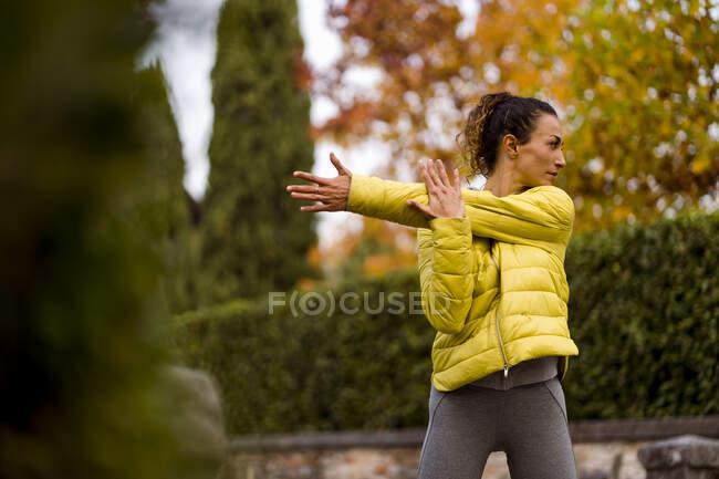 Доросла жінка розтягує руку, стоячи в парку. — стокове фото