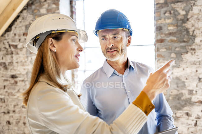 Businesswoman wearing hardhat giving instruction to building contractor while working at construction site — Stock Photo