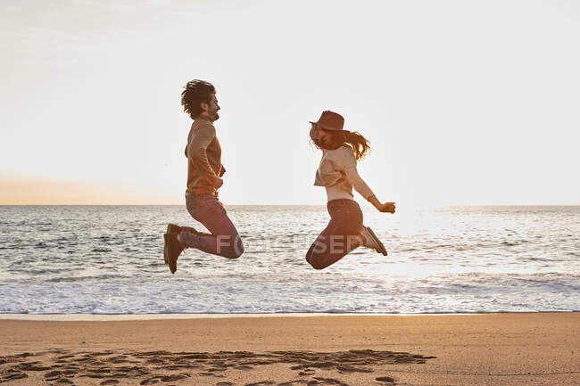 Couple playing while jumping at beach during sunrise — Stock Photo