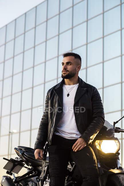 Hombre guapo en chaqueta de cuero apoyado en la motocicleta contra el edificio moderno - foto de stock