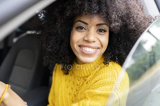 Щаслива жінка посміхається за кермом. — стокове фото