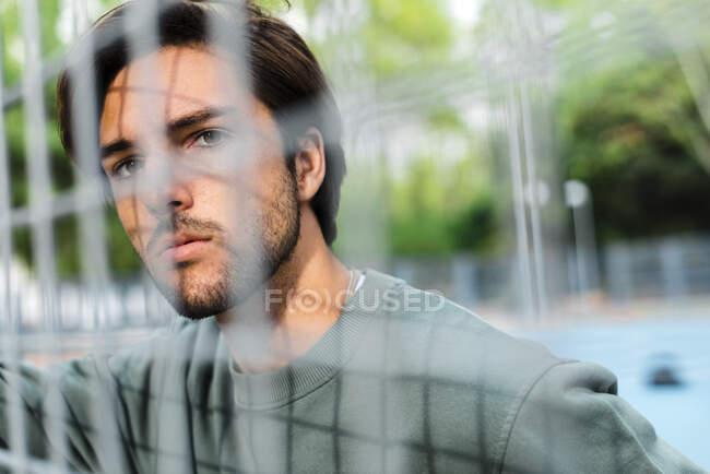 Pensativo joven apuesto hombre mirando hacia otro lado visto a través de valla en la cancha de baloncesto - foto de stock