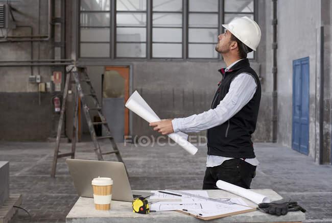 Architecte masculin tenant plan levant les yeux tout en se tenant debout dans le bâtiment — Photo de stock