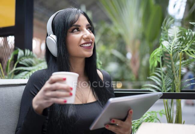 Ragazza premurosa che ascolta musica mentre prende un caffè al caffè — Foto stock