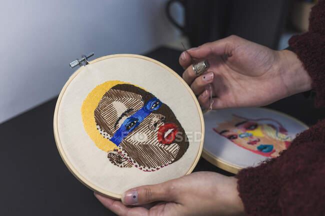 Manos de mujer joven bordando en tela en el marco en el estudio - foto de stock