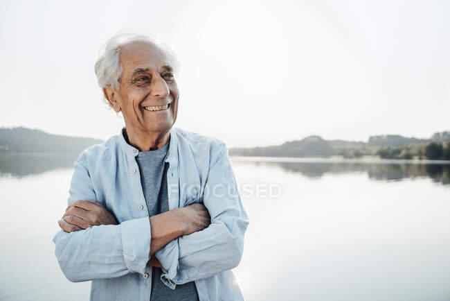 Щасливий чоловік, що відвів погляд, стоячи, схрестивши руки на воду. — стокове фото