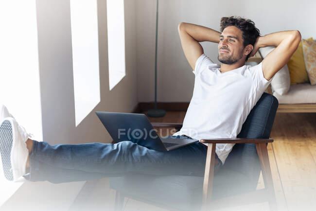 Чоловік, що тримає руки за головою, відпочиває, сидячи вдома на кріслі. — стокове фото
