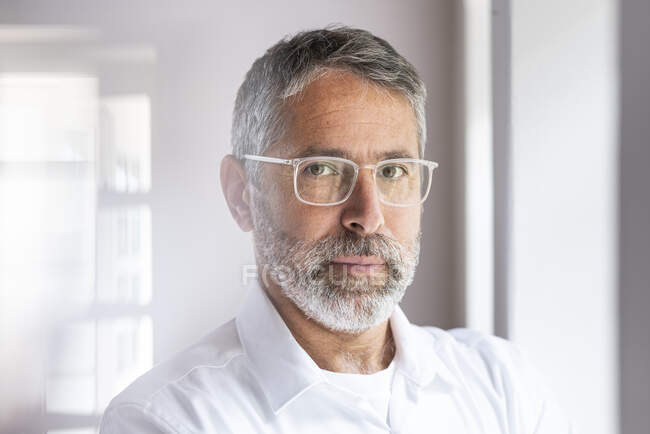 Confident businessman wearing eyeglasses staring while standing at home — Stock Photo