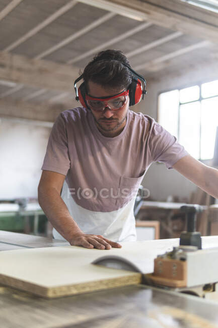 Young male carpenter cutting wood using table saw while working in workshop — Stock Photo