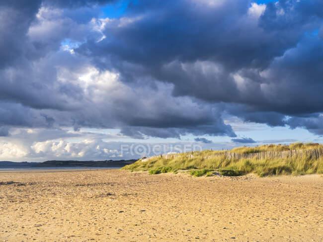 Playa de Sainte-Anne la Palud contra el cielo nublado - foto de stock