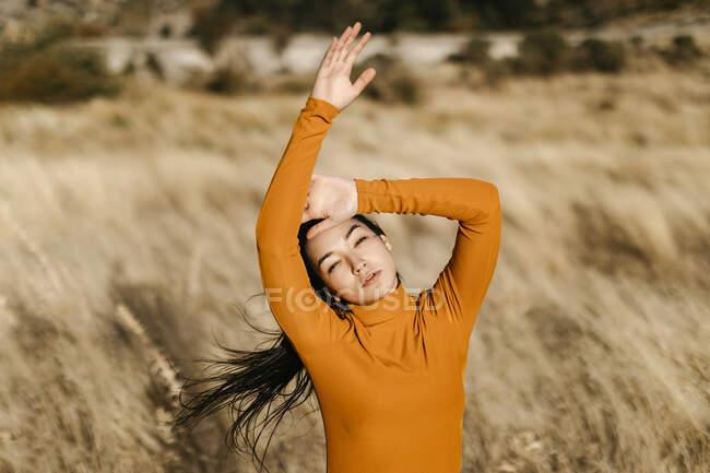 Mulher bonita com braços levantados em pé no campo durante o dia ventoso — Fotografia de Stock